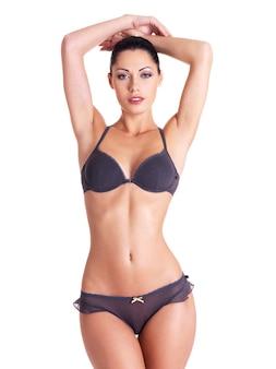 Młoda kobieta z pięknym szczupłym idealnym ciałem w bikini na białym tle