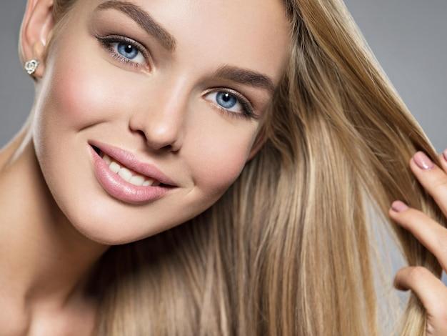 Młoda kobieta z pięknym uśmiechem. twarz modelka o niebieskich oczach. całkiem wspaniała dziewczyna o blond włosach - pozowanie