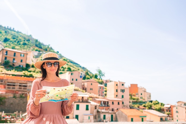 Młoda kobieta z pięknym widokiem przy starą wioską riomaggiore, cinque terre, liguria