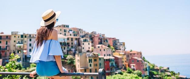 Młoda kobieta z pięknym widokiem przy starą wioską w cinque terre, liguria, włochy.