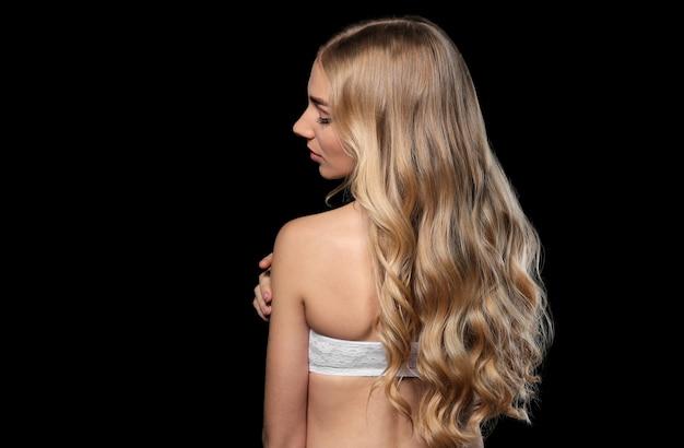 Młoda kobieta z pięknymi kręconymi włosami na ciemnym