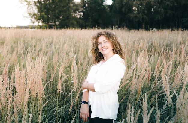 Młoda kobieta z pięknymi kręconymi włosami stoi w parku wśród wysokiej trawy i uśmiecha się.