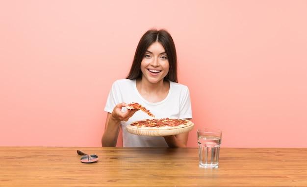 Młoda kobieta z pizzą w stole