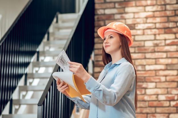 Młoda kobieta z planem budowy w pomieszczeniu