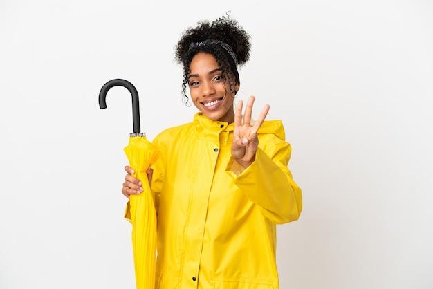 Młoda kobieta z płaszczem przeciwdeszczowym i parasolem na białym tle szczęśliwa i licząca trzy palcami