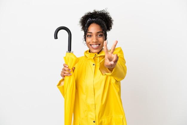 Młoda kobieta z płaszczem przeciwdeszczowym i parasolem na białym tle uśmiecha się i pokazuje znak zwycięstwa