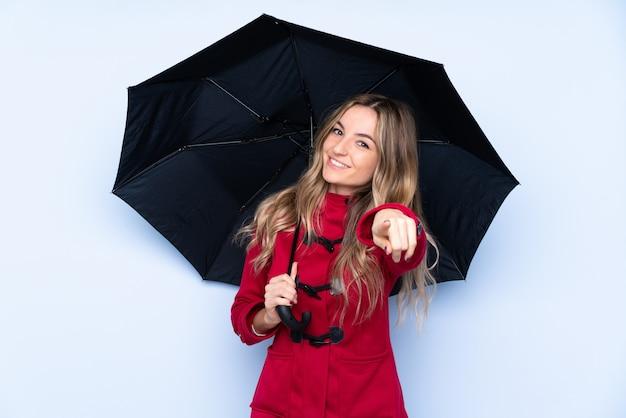 Młoda kobieta z płaszczem zimowym i trzymając parasol wskazuje palcem na ciebie z pewnym siebie wyrazem twarzy