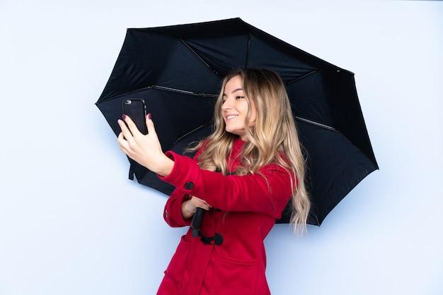 Młoda kobieta z płaszczem zimowym, trzymając parasol i telefon komórkowy