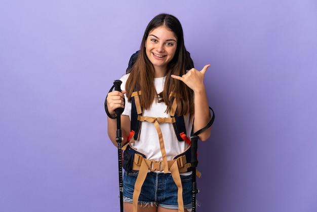 Młoda kobieta z plecakiem i kijkami trekkingowymi na białym tle na fioletowej ścianie dzięki telefonowi gestowi. oddzwoń do mnie znak