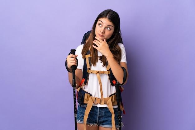 Młoda kobieta z plecakiem i kijkami trekkingowymi na białym tle na fioletowej ścianie, mając wątpliwości