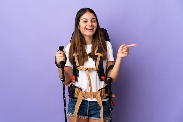 Młoda kobieta z plecakiem i kijkami trekkingowymi na białym tle na fioletowej ścianie wskazując palcem w bok i prezentuje produkt