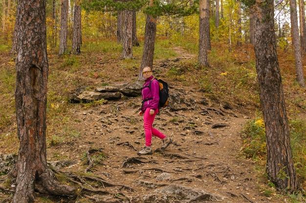 Młoda kobieta z plecakiem jest zaangażowana w trekking w jesiennym lesie