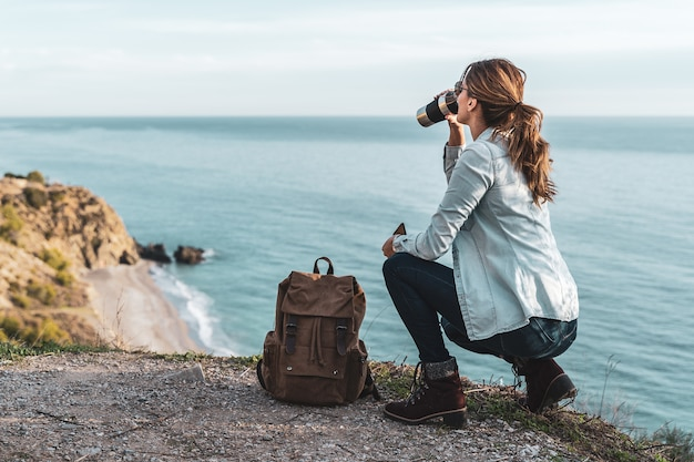 Młoda kobieta z plecakiem, picia kawy i zwiedzania wybrzeża w piękny dzień. pojęcie eksploracji i przygód