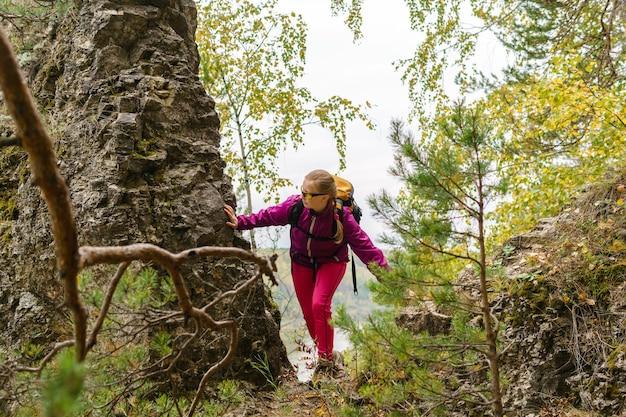 Młoda kobieta z plecakiem zaangażowana w trekking po górskim szlaku torującym sobie drogę
