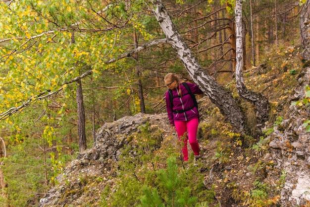Młoda kobieta z plecakiem zajmuje się trekkingiem górskim szlakiem wśród jesiennego lasu