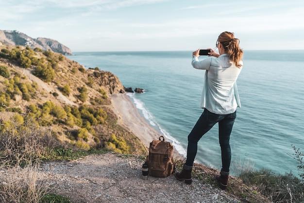 Młoda kobieta z plecakiem, zwiedzanie i fotografowanie wybrzeża w piękny dzień. pojęcie eksploracji i przygód