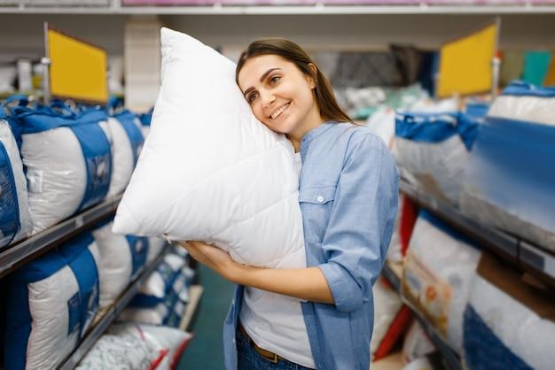 Młoda kobieta z poduszkami w sklepie z pościelą. kobieta kupuje artykuły domowe na rynku, pani w sklepie z pościelą