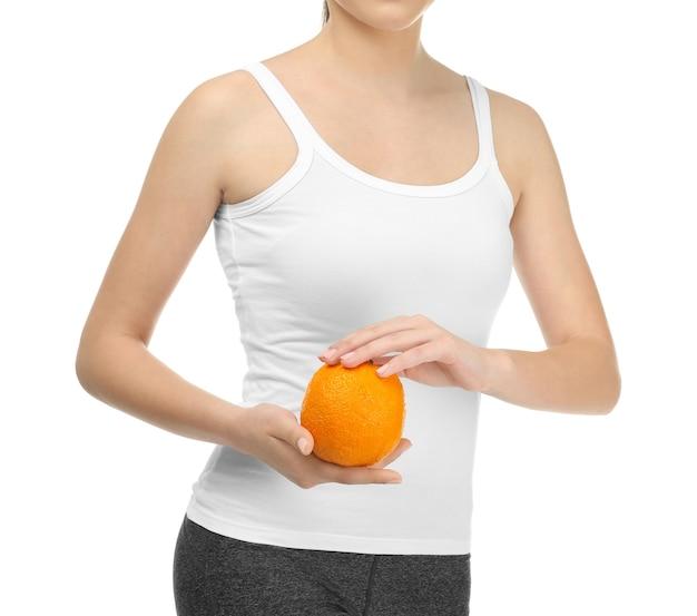 Młoda kobieta z pomarańczą na białej powierzchni. koncepcja diety