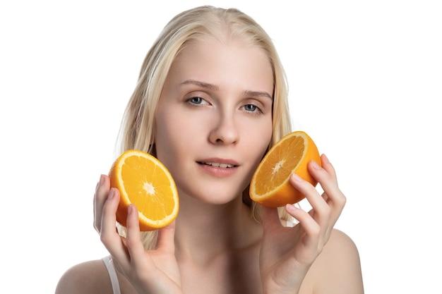 Młoda kobieta z pomarańczami w dłoniach.