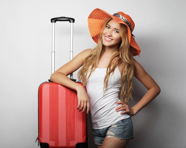 Młoda kobieta z pomarańczową torbą podróżną