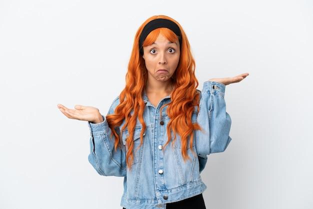 Młoda kobieta z pomarańczowymi włosami na białym tle ma wątpliwości podczas podnoszenia rąk