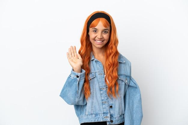 Młoda kobieta z pomarańczowymi włosami na białym tle pozdrawiająca ręką ze szczęśliwym wyrazem twarzy