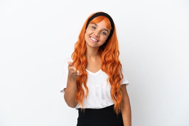 Młoda kobieta z pomarańczowymi włosami na białym tle, ściskając ręce, aby zamknąć dobrą ofertę