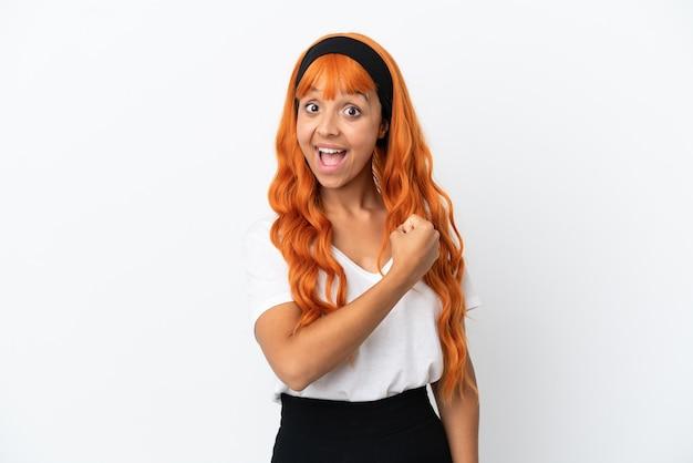 Młoda kobieta z pomarańczowymi włosami na białym tle świętująca zwycięstwo