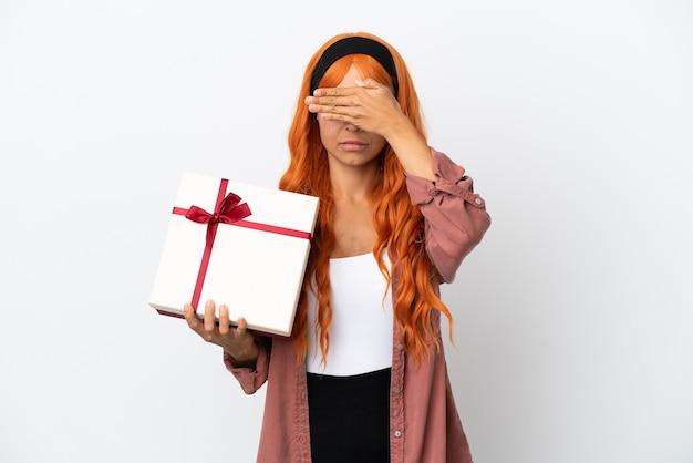 Młoda kobieta z pomarańczowymi włosami trzyma prezent na białym tle na białym tle zasłaniając oczy rękami. nie chcę czegoś widzieć