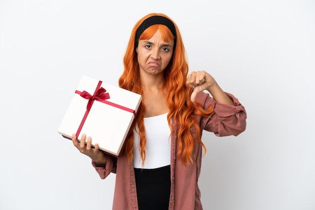 Młoda kobieta z pomarańczowymi włosami trzyma prezent na białym tle pokazując kciuk w dół z negatywnym wyrazem twarzy