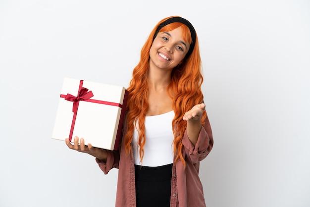 Młoda kobieta z pomarańczowymi włosami trzyma prezent na białym tle, ściskając ręce, aby zamknąć dobrą ofertę