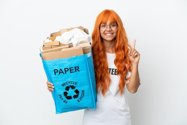 Młoda kobieta z pomarańczowymi włosami trzyma torbę do recyklingu pełną papieru do recyklingu na białym tle pokazując i podnosząc palec na znak najlepszych