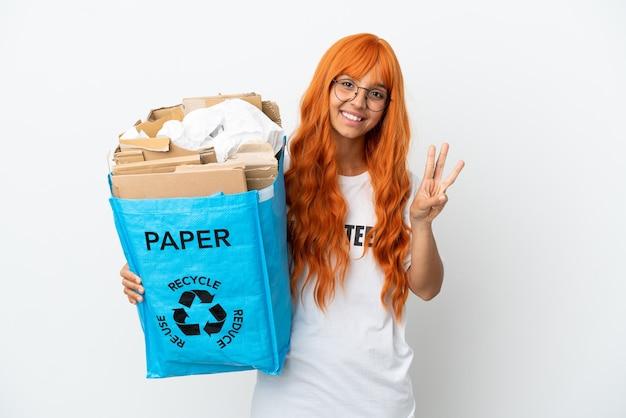 Młoda kobieta z pomarańczowymi włosami trzyma torbę do recyklingu pełną papieru do recyklingu na białym tle szczęśliwa i licząca trzy palcami