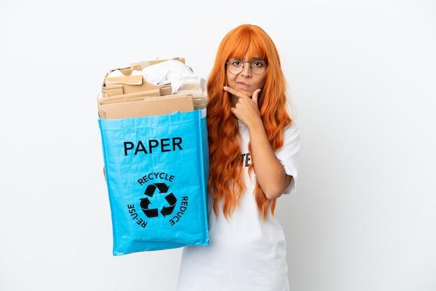 Młoda kobieta z pomarańczowymi włosami trzyma worek do recyklingu pełen papieru do recyklingu na białym tle na myślenie na białym tle