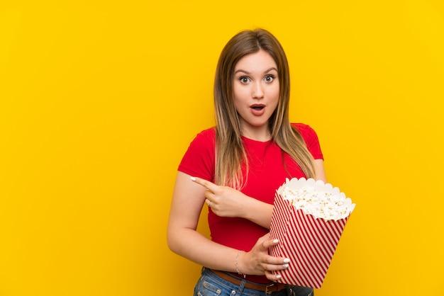 Młoda kobieta z popcorns nad menchii ścianą zaskakującą i wskazuje stroną