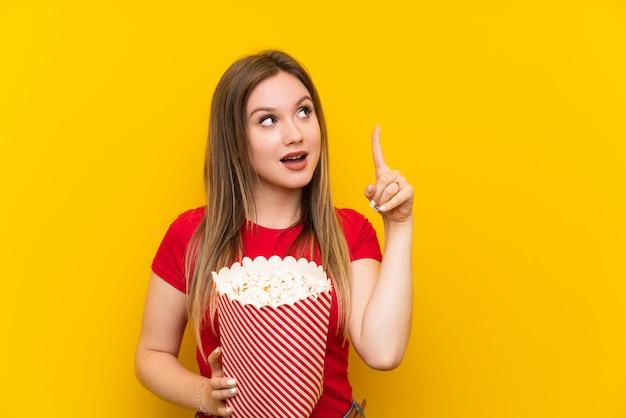 Młoda kobieta z popcorns nad różową ścianą zamierza zrealizować rozwiązanie, podnosząc palec