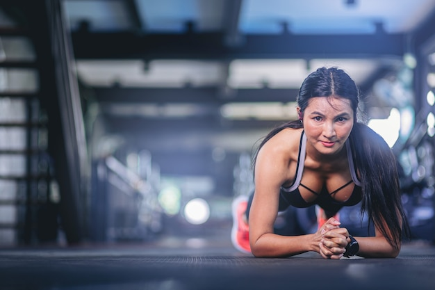 Młoda kobieta z potem robi ćwiczenia z deskowaniem w siłowni fitness