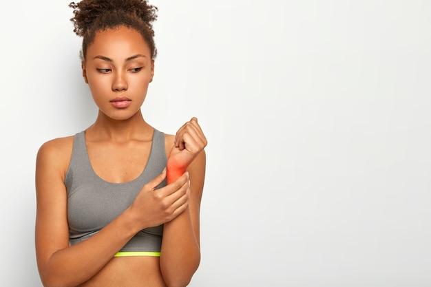 Młoda kobieta z poważnymi kręconymi włosami ma kontuzję nadgarstka, podnosi rękę z czerwonym ogniskiem wskazującym miejsce bólu, cierpi na zwichnięcie po treningu, nosi luźny top, pozuje na białej ścianie z miejscem na kopię
