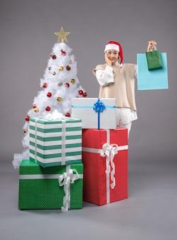 Młoda kobieta z prezentami świątecznymi na szaro