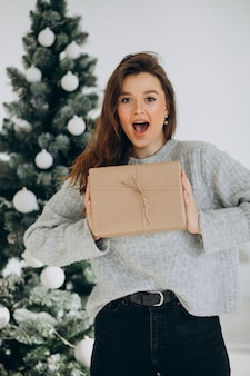 Młoda kobieta z prezentami świątecznymi przez choinkę