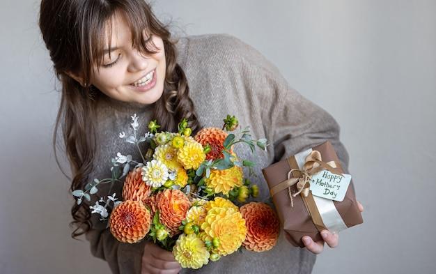 Młoda kobieta z prezentem na dzień matki i bukietem kwiatów w dłoniach