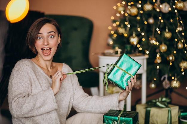 Młoda kobieta z prezentem świątecznym przez choinkę