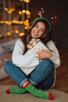 Młoda kobieta z prezentem, uśmiechając się