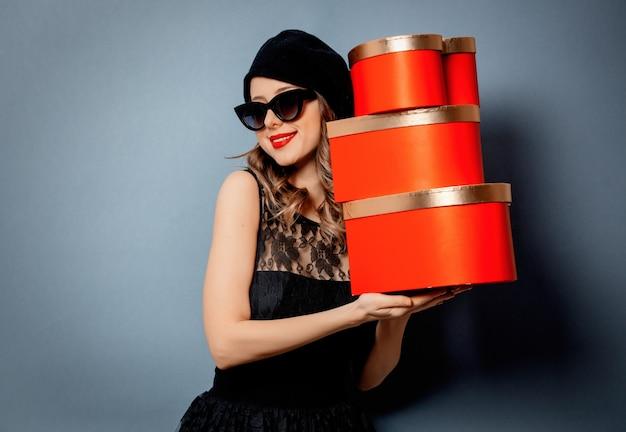 Młoda kobieta z prezentów pudełkami na szarości ścianie