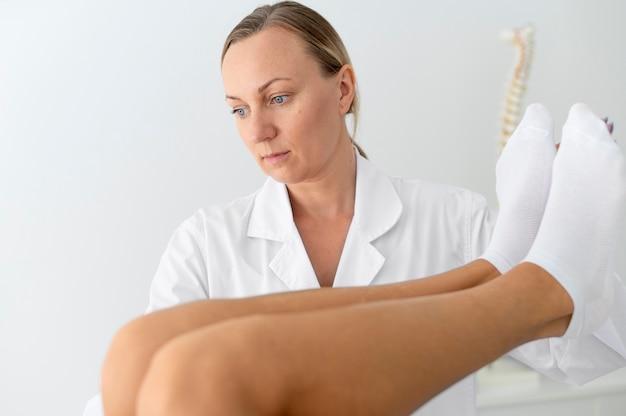 Młoda kobieta z problemami z plecami podczas zabiegu fizjoterapeutycznego
