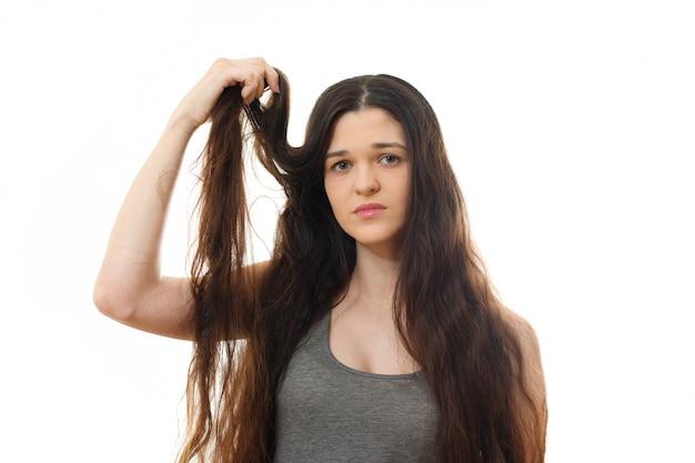 Młoda kobieta z problemem włosów. na białym tle