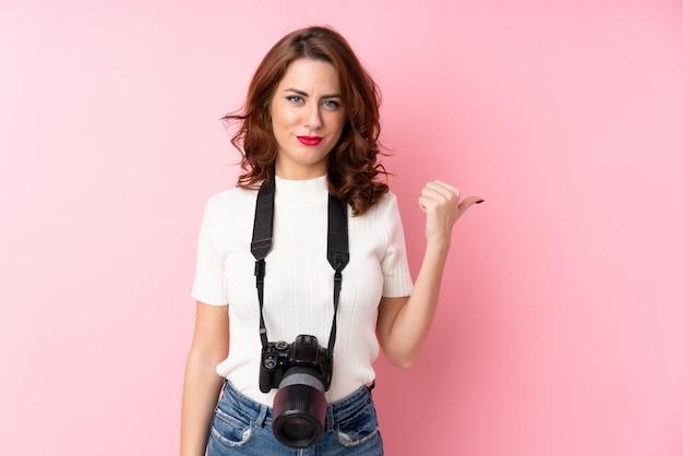 Młoda kobieta z profesjonalnym aparatem i wskazując na bok