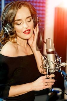 Młoda kobieta z profesjonalnym mikrofonem w studiu nagrań. wokalistka w studio.