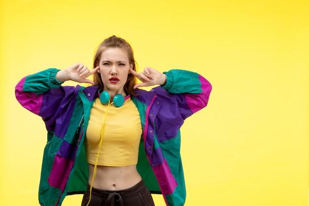 Młoda kobieta z przodu w żółtych koszulowych czarnych spodniach i kolorowej kurtce z kolorowymi słuchawkami