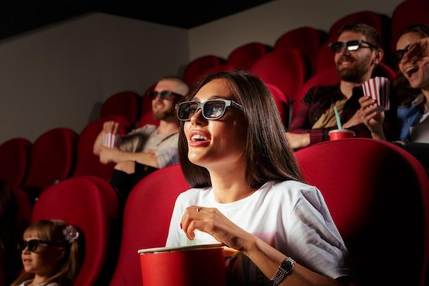 Młoda kobieta z przyjaciółmi ogląda film w kinie